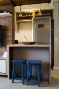 """Cozinha americana com """"janela"""" entre a cozinha e a sala de estar com iluminação, banquetas de madeira, prateleira suspensa e balcão gourmet."""